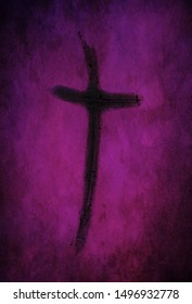 Ash cross made from burned palm crosses isolated on purple and black speckled background. Ash Wednesday, repentance and hope in Christ concept.
