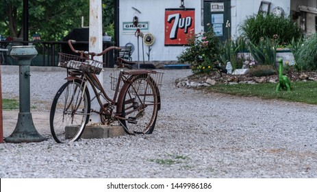 Ash Grove, MO/USA - June 7, 2018: Old Vintage Bicycle With Antique Soft Drink Beverage Sign In Background On Historic Route 66. Road Trip Back In Time At Gary's Gay Parita In Missouri.