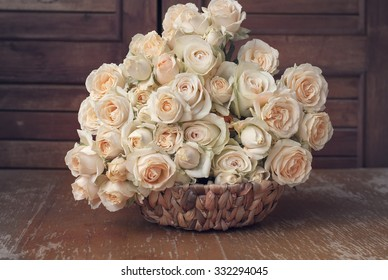 Ash and tea roses in a wicker basket on an old shabby table.