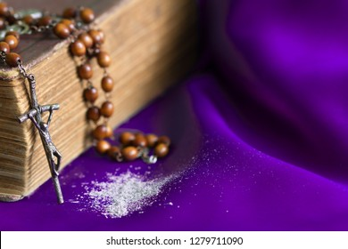 Ash Wednesday religion concept on violet fabric background with rosary