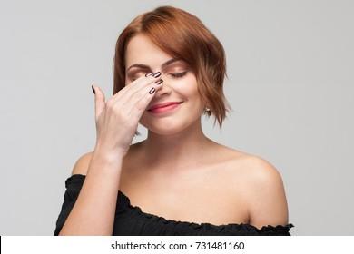 Ashamed female beauty. Bashful youth. Shy woman portrait on grey background closeup, timid smiling girl. Joke communication facial expression concept