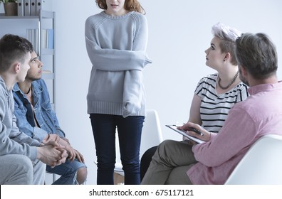 Ashamed girl sharing her issues with others, at group therapy