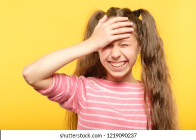 ashamed smiling girl covering her forehead with a hand. embarrassment and shame emotion.