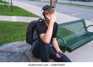 Ashamed teenager sitting on a rock outside of a school while listening to music.