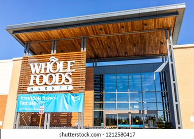 Ashburn, USA - October 19, 2018: New, modern, large Whole Foods Market sign on exterior building in city in Virginia with people, blue Amazon Prime delivery sign, entrance