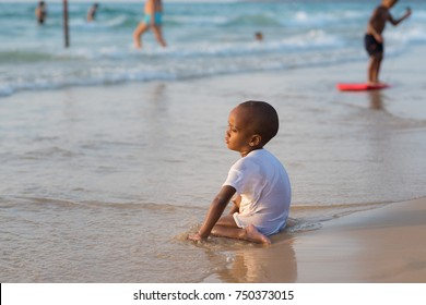 Ashdod Beach, ISRAEL - SEPTEMBER 22, 2017 Dark skin little boy.Cute little African Israeli kid in wet clothes on beach and  background .