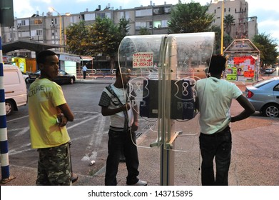 ASHDOD, ISR - AUG 28:Sudanese refugees men talk on a public phone on August 28 2010. There are currently an estimated 60,000 African migrants in Israel.