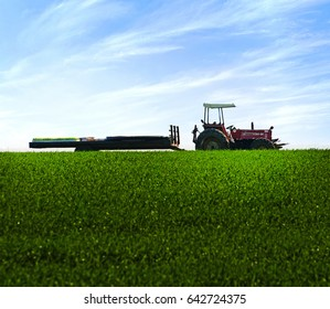 Ashdod, Israel - March 19, 2012:A tractor in a green field with a cart and plants