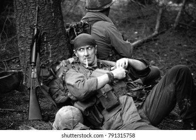 Ashdown Forest 2001 a reenactor of the Vietnam War Society takes a rest and pulls on a cigarette he is armed with an M16 rifle. Image taken in Kent in Sept 2002