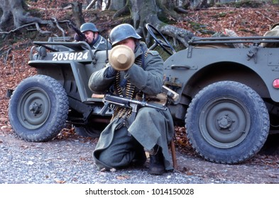 Ashdown Forest England November 1998 a WW2 reenactor in full German uniform fires a panzerfaust in front of a WW2 Jeep in a forest setting.