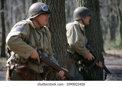 Ashdown Forest Kent 1998. Two unidentified reenactors in the period uniform of WW2 US Riflemen stand in woodland in a re-enactment of the Ardennes Campaign 1944.
