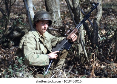 Ashdown Forest Kent England 1998. A young reenactor dressed in the uniform of a WW2 US infantryman holds a Browning Automatic rifle while crouching in dense woodland.