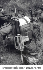 Ashdown Forest Kent England 2003. A replica Colt M4 rifle leaning against a backpack in a combat environment.