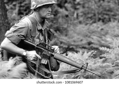 Ashdown Forest Kent UK 1998. An unidentified reenactor of the Vietnam War walks in a wood dressed in the uniform of a US Rifleman holding an M16 rifle at a re-enactment of the Battle of Dewey Canyon.