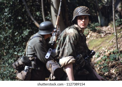 Ashdown Forest Kent UK 1998. Two unidentified WW2 reenactors wear the period uniform of SS Infantrymen they stand in woodland at a reenactment of the Battle of Ardennes 1944.