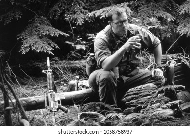 Ashdown Forest Kent UK 2001. An unidentified reenactor of the Vietnam War wears period uniform of a US Sargent he sits in conversation in woodland at a re-enactment of the Battle of Dewey Canyon.