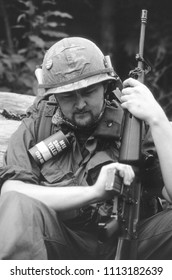 Ashdown Forest Kent UK 2001. An unidentified reenactor of the Vietnam War sits in woodland holding an M16 rifle wearing the period uniform of a US Rifleman of 1970 at a reenactment event.