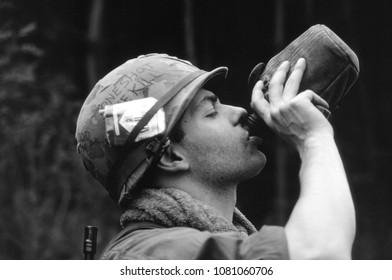Ashdown Forest Kent UK 2002. An unidentified reenactor of the Vietnam War takes a drink form a water bottle and wears the uniform of a US rifleman at a re-enactment of the Battle of Dewey Canyon 1968.