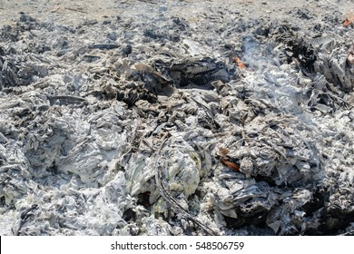 the ashes of the paper and the fire in the field still burning on ashes.
