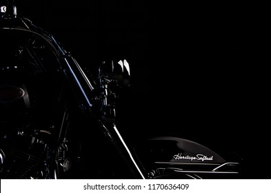 Asheville, NC - August 2018: Harley Davidson Heritage Softail front fork and wheel isolated by light with black background