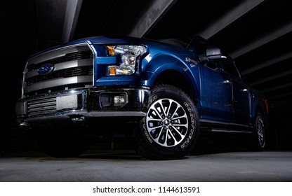 Asheville, NC - July 2018: Ford F150 isolated by light with black background in parking garage