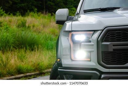 Asheville, NC - July 2018: Ford F150 Raptor headlights and grill isolated with grass background