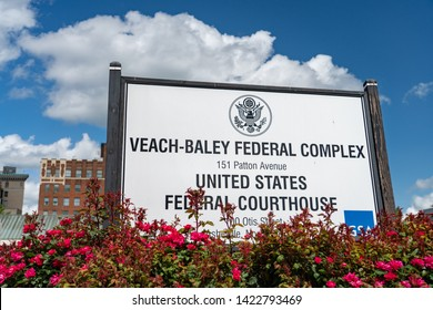 Asheville, NC / USA - May 10, 2019: This is the sign outside at the Veach-Baley Federal Complex in Asheville, NC. Shows buildings behind the sign and flowers in front of the sign.