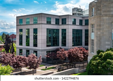 Asheville, NC / USA - May 10, 2019: This is the Veach-Baley Federal Complex in Asheville, NC. Shows the building with all the glass windows and trees in the courtyard.
