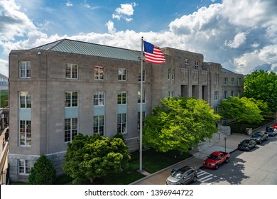 Asheville, NC / USA - May 11, 2019: This is a color photo of the Federal Building in Asheville, NC with the flag flying and blue sky and clouds behind the flag.