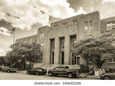 Asheville, NC / USA - May 11, 2019: This is a sepia toned photo of the Federal Building in Asheville, NC with the flag flying and blue sky and clouds behind the flag.