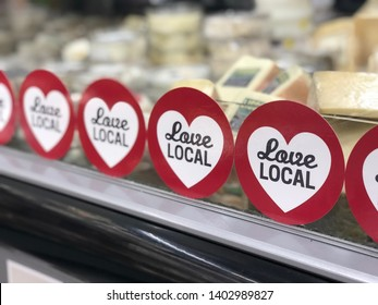 """Asheville, NC / USA - May 20, 2019: This photo is of a display of local cheese that has a """"Love Local"""" sticker on the window of the display. There are many stickers covering the window of the display."""