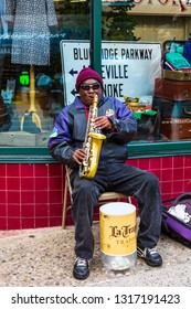 ASHEVILLE, NC, USA-2/16/19: A saxophonist sitting on folding chair and busking.