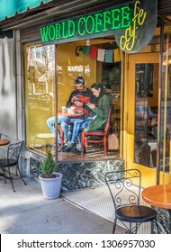 ASHEVILLE, NC, USA-2/3/19: A couple sits in front display window of coffee shop, at small table, each looking at smart phones.