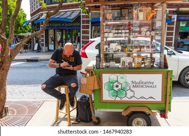 ASHEVILLE, NC, USA-27 JULY 2019: A tattooed man sitting on a stool in downtown Asheville sells Meditative Medicinals.
