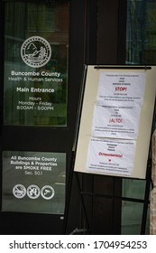 Asheville, North Carolina - 13 April 2020: Multilingual announcements outside of the door of the Buncombe County Health Department stating entry restrictions during the Covid-19 pandemic