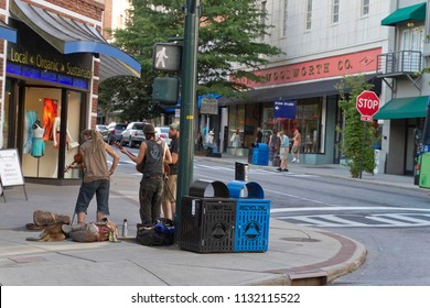 ASHEVILLE, NORTH CAROLINA, AUGUST 17, 2017: Street scene in downtown Asheville, including Woolworth Walk (art gallery), buskers playing music with a snoozing dog, and tourists