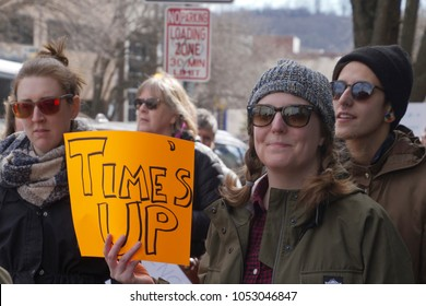 "ASHEVILLE, NORTH CAROLINA - JANUARY 20, 2018: Women marching in the 2018 Women's March show a sign directed toward Trump, the GOP and sexism saying ""Time's Up"" in downtown Asheville, North Carolina"