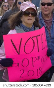 """ASHEVILLE, NORTH CAROLINA - JANUARY 20, 2018: A woman holds a large pink signing saying """"Vote! GOP Out 2018"""" amid a crowd of women marching in the Women's March in downtown Asheville, North Carolina"""