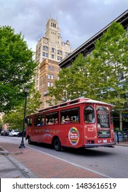 Asheville, North Carolina, United States - August 19, 2019: Trolley Bus with historic Jackson Building in background - Pack Square, Downtown Asheville
