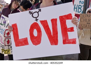 """Asheville, North Carolina, USA - April 2, 2016:  Close up of a sign that says """"LOVE"""" along with the trans symbol at a HB2 protest rally of the new NC law"""