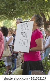 """ASHEVILLE, NORTH CAROLINA, USA - AUGUST 5, 2013:  A woman at a Moral Monday rally holds a sign saying """"VOTE THEM OUT!"""""""