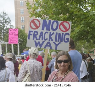 Asheville, North Carolina, USA - August 4, 2014:  Woman at a Moral Monday rally holds a sign protesting fracking amid a gathering crowd of demonstrators on August 4, 2014 in downtown Asheville, NC