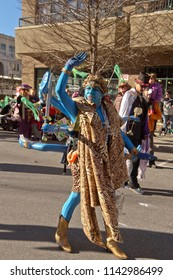 ASHEVILLE, NORTH CAROLINA, USA - FEBRUARY 7, 2016: Woman creatively dressed as the blue, eight armed Hindu goddess Kali waves to bystanders in the Mardi Gras Parade in downtown Asheville