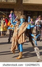 ASHEVILLE, NORTH CAROLINA, USA - FEBRUARY 7, 2016: Woman creatively costumed as Kali, the blue, eight armed Hindu goddess of Death, entertains the crowd in the 2016 Mardi Gras Parade in  Asheville