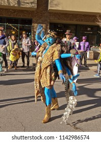 ASHEVILLE, NORTH CAROLINA, USA - FEBRUARY 7, 2016: Woman creatively costumed as Kali, the blue, eight armed, Hindu goddess of Death, entertains the crowd in the Mardi Gras Parade in downtown Asheville