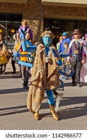 ASHEVILLE, NORTH CAROLINA, USA - FEBRUARY 7, 2016: Woman creatively costumed as Kali, the blue, eight armed, Hindu goddess of Death, entertains the crowd in the 2016 Mardi Gras Parade in Asheville