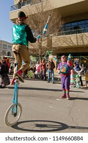 ASHEVILLE, NORTH CAROLINA, USA - FEBRUARY 7, 2016: Colorful jugglers, one balanced on a unicycle, swap juggling pins back and forth between them to entertains the crowd in the 2016 Mardi Gras Parade