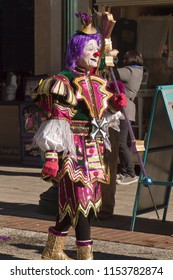ASHEVILLE, NORTH CAROLINA, USA - FEBRUARY 7, 2016: Colorful and creatively costumed Mardi Gras clown carries a septor in the 2016 Mardi Gras Parade in downtown Asheville