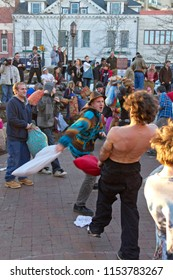 ASHEVILLE, NORTH CAROLINA, USA - FEBRUARY 14, 2013: People having fun smacking each other with pillows at the rowdy, free-for-all annual Valentine's Day pillow fight in downtown Asheville