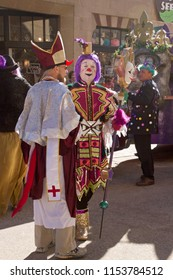 ASHEVILLE, NORTH CAROLINA, USA - FEBRUARY 7, 2016: A colorful and creatively costumed Mardi Gras clown converses in the street with a costumed Bishop in the tradiitional 2016 Mardi Gras Parade